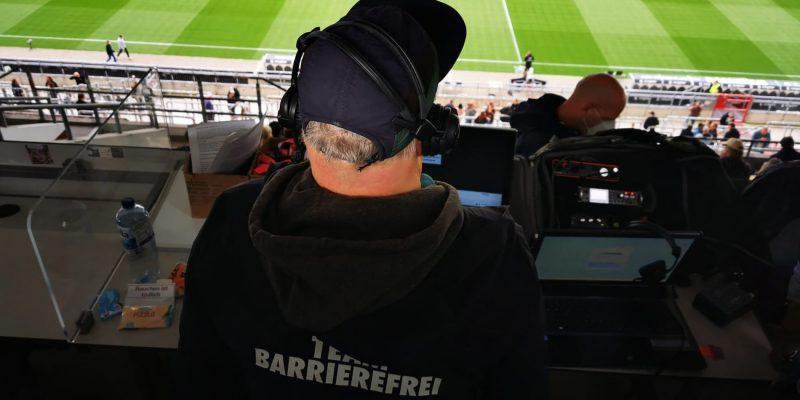 Person von hinten fotografiert, die einen Pullover mit Team Barrierefrei-Aufschrift und Kopfhörer trägt. Die Person guckt dabei auf das Spielfeld.