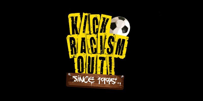 """Gelbe-schwarzer """"Kick Racism Out""""-Schriftzug mit einem braun-weißen """"Since 1995""""-Schild in Holzoptik sowie einem schwarz-weißen Fußball garniert."""